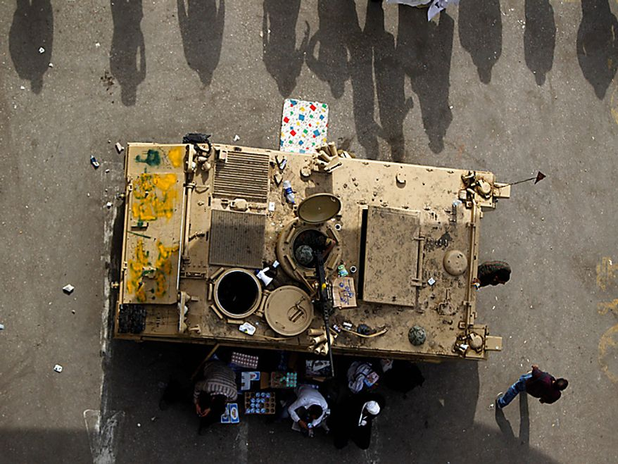 People line up next to a military vehicle in Cairo's main square Thursday, Feb. 3, 2011. (AP Photo/Tara Todras-Whitehill)