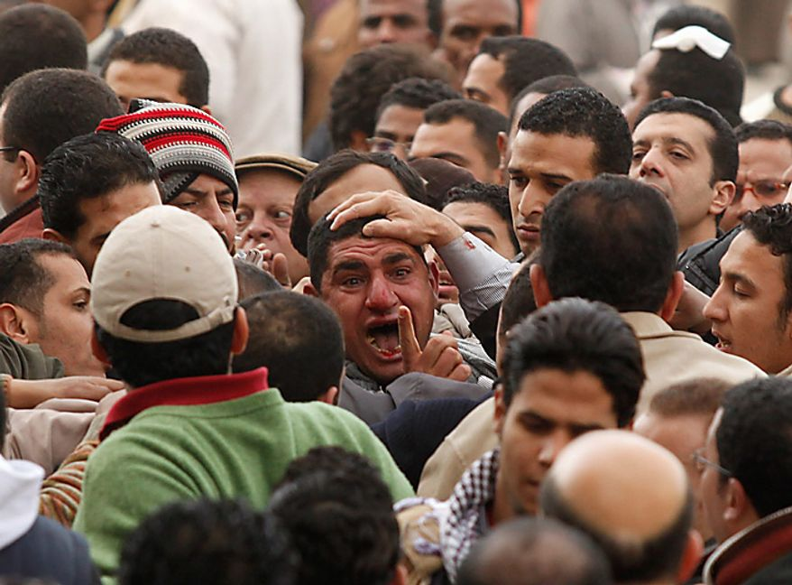 Anti-government demonstrators grab a man they suspect to be a supporter of Egyptian President Hosni Mubarak in Cairo's Tahrir Square Thursday, Feb. 3, 2011. (AP Photo/Victoria Hazou)