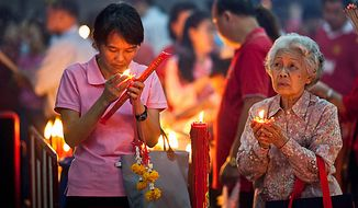 Thai Buddhists offer prayers at a temple in Chinatown Thursday, Feb. 3, 2011, in Bangkok, Thailand. Feb. 3, 2011, marks the start of the Chinese New Year, the year of the rabbit. (AP Photo/David Longstreath)