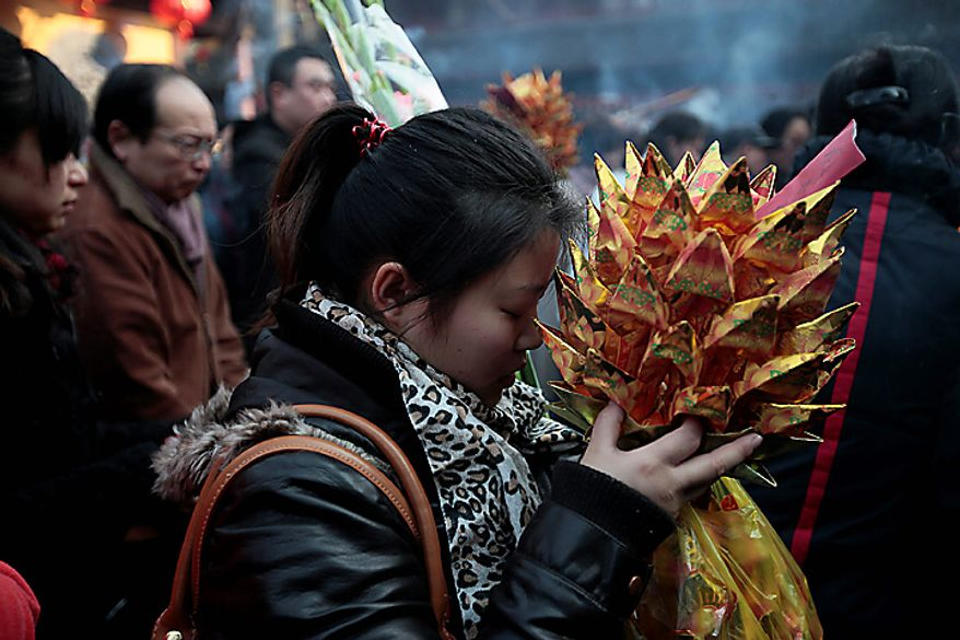 A worshipper offers the first prayer of the lunar new year at a temple Thursday, Feb. 3, 2011, in Shanghai, China. According to the Chinese Zodiac, 2011 is the Year of the Rabbit. (AP Photo/Eugene Hoshiko)