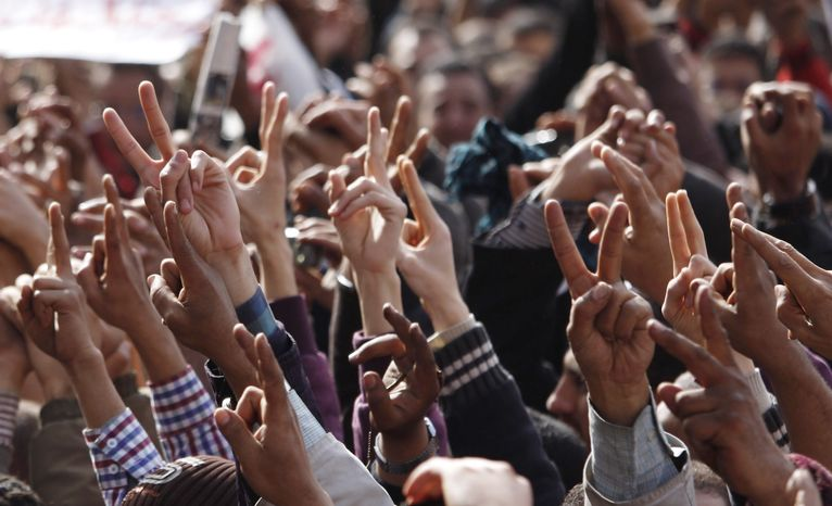 Anti-government protesters rise their hands in the victory sign in Cairo's Tahrir Square, Friday, Feb. 4, 2011. The Egyptian military guarded thousands of protesters pouring into Cairo's main square on Friday in an attempt to drive out President Hosni Mubarak after a week and half of pro-democracy demonstrations. (AP Photo/Emilio Morenatti)