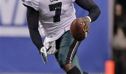 FILE - In this Jan. 9, 2011, file photo, Philadelphia Eagles quarterback Michael Vick scrambles during the second half of an NFL wild card playoff football game against the Green Bay Packers in Philadelphia. After missing two seasons serving a federal sentence for dogfighting, then spending most of the previous year as a seldom-used backup in Philadelphia, Vick was back at his best in 2010 and was selected as The Associated Press 2010 NFL Comeback Player of the Year on Saturday, Feb. 5, 2011.  (AP Photo/Miles Kennedy, File)