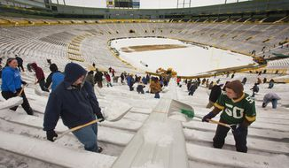 Green Bay Packers fans shovel out Lambeau Field on Monday, Feb. 7, 2011, in Green Bay, Wis., in preparation for a rally on Tuesday to celebrate the team's Super Bowl victory on Sunday. (AP Photo/Mike Roemer)
