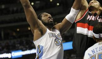 Denver Nuggets center Nene (31) goes to the basket past Portland Trail Blazers center Chris Johnson during the fourth quarter of an NBA basketball game in Denver, Wednesday, Feb. 2, 2011. The Nuggets won 109-90. (AP Photo/Barry Gutierrez)