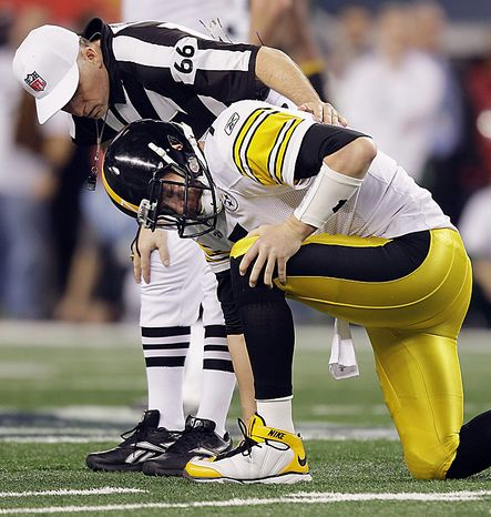 The Pittsburgh Steelers' Ben Roethlisberger holds his leg after a play against the Green Bay Packers as referee Walt Anderson (66) checks on him during the first half of the NFL Super Bowl XLV football game on Sunday, Feb. 6, 2011, in Arlington, Texas. (AP Photo/Chris O'Meara)
