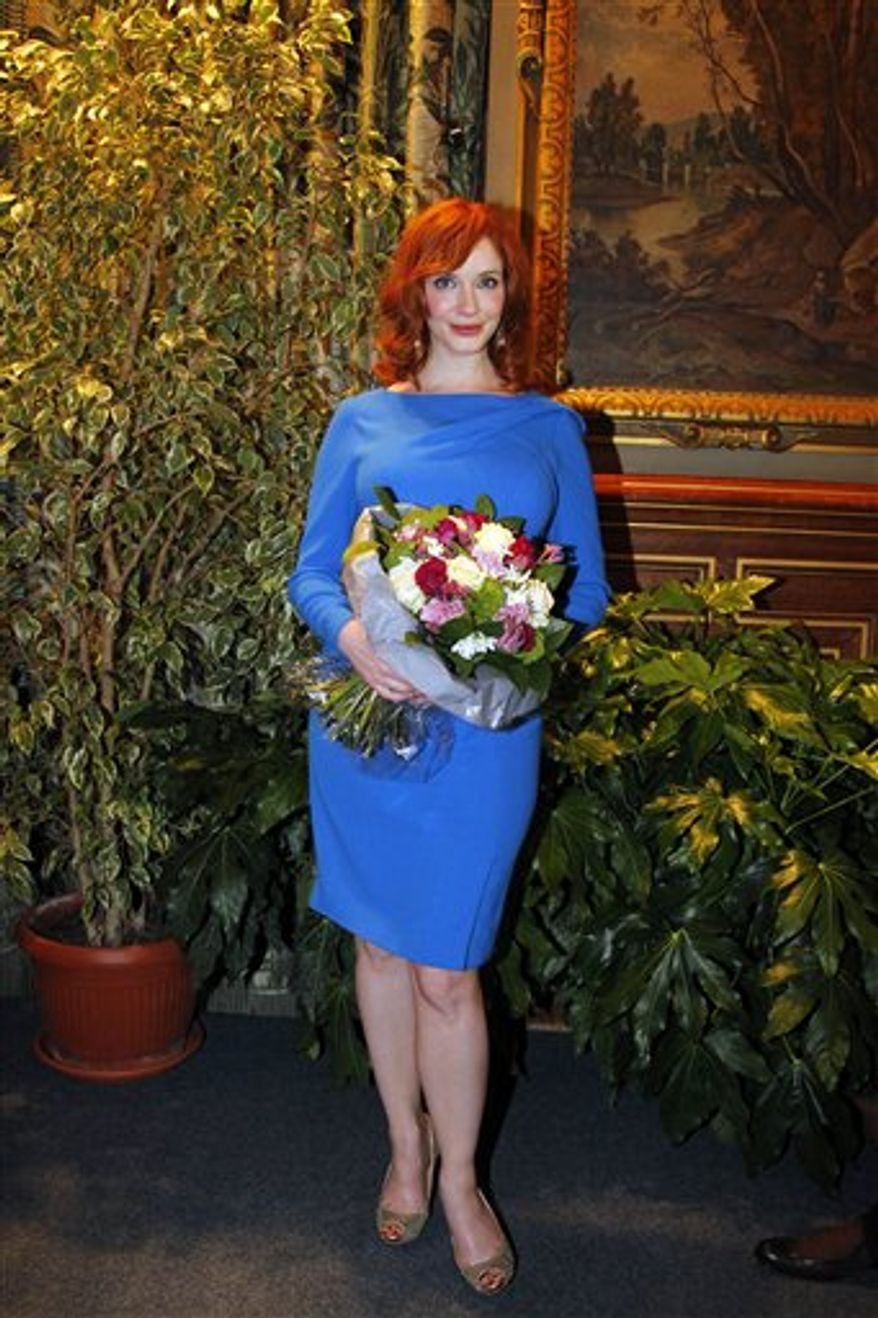 U.S. actress Christina Hendricks, star of the hit TV series Mad Men poses as U.S. creator, executive producer and writer of the series Matthew Weiner, unseen, received the Vermeil Medal of the City of Paris,  in  City Hall,  Paris Tuesday, Feb. 8, 2011. (AP Photo/Francois Mori)