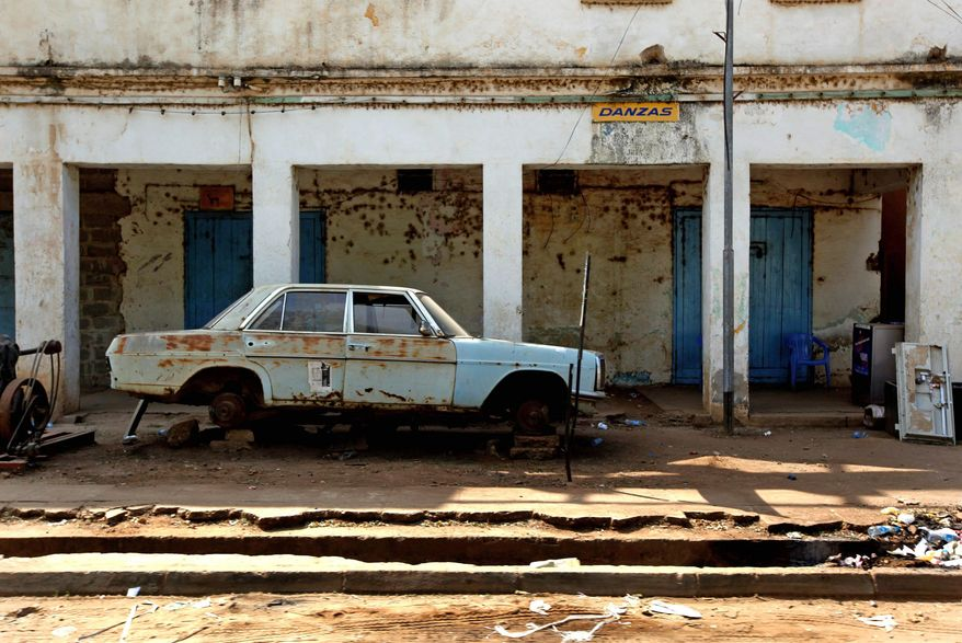 A rusted car sits on blocks in run-down surroundings in Juba. Decades of war have kept southern Sudan poor and decrepit. (Associated Press)