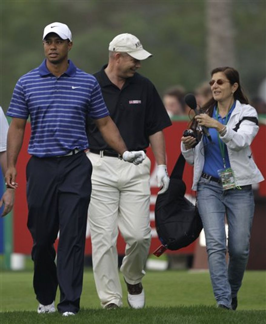 A journalist interviews American army officer Lt. Col. Micheal Rowells, center, as he plays with Tiger Woods, left, during the Pro-Am at the Emirates Golf Club a day ahead of Dubai Desert Classic golf tournament in Dubai, United Arab Emirates, Wednesday Feb. 9, 2011. (AP Photo/Kamran Jebreili)
