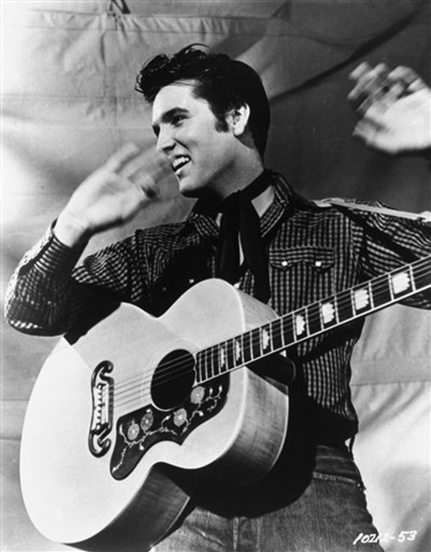 FILE - Elvis Presley poses with his Gibson J-200 guitar in an MGM studio publicity photo from the 1950s.  Elvis Presley Enterprises said Wednesday Feb. 9, 2011 it's suing men in Florida and England on claims of copyright infringement and illegal sale of a DVD and CD box set of recordings and footage of the singer's performances.   (AP Photo/MGM, File )