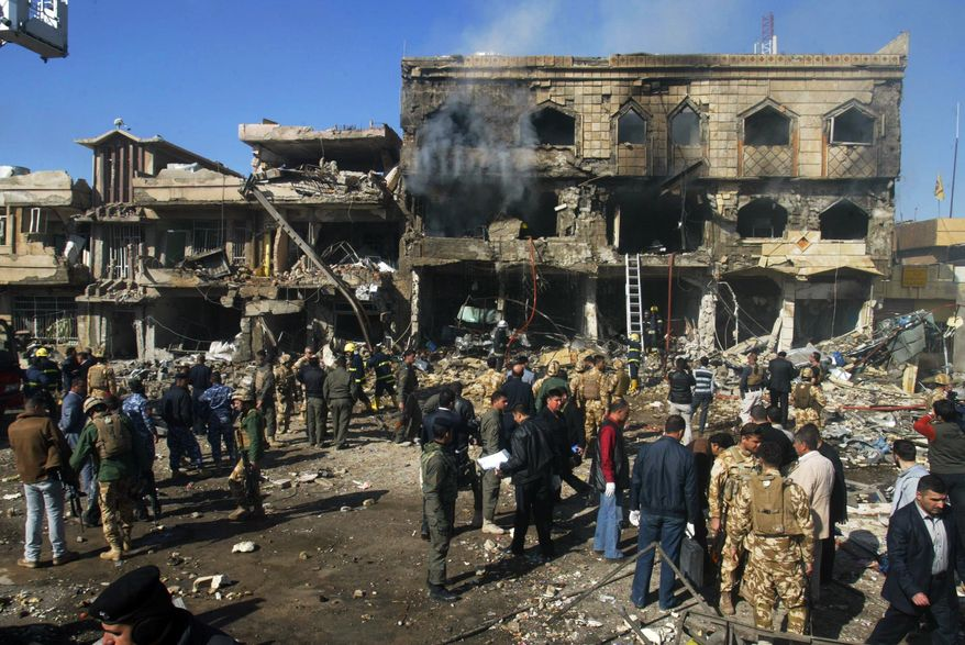 Security forces, emergency responders and civilians stand near a destroyed building after a car-bomb attack in Kirkuk, Iraq, 180 miles north of Baghdad, on Wednesday, Feb. 9, 2011. (AP Photo/Emad Matti)