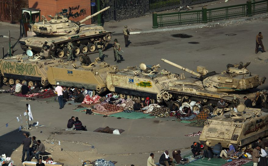 Anti-Mubarak protesters are seen next to Egyptian army tanks and armored vehicles near Tahrir Square in Cairo on Wednesday, Feb. 9, 2011. Protesters appear to have settled in for a long standoff, turning the square into a makeshift village with tens of thousands coming every day, with some sleeping in tents made of blankets and plastic sheeting. (AP Photo/Emilio Morenatti)