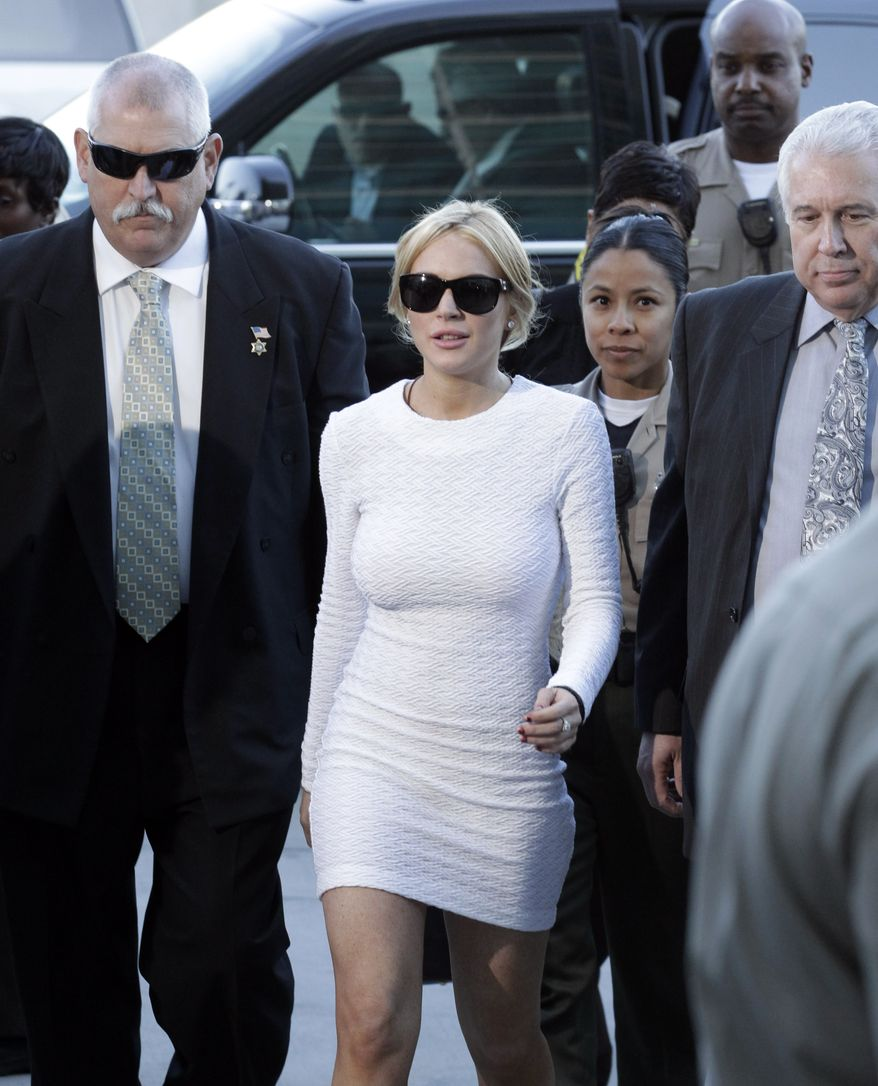 Actress Lindsay Lohan (center) arrives Wednesday at the LAX Airport Courthouse in Los Angeles to be arraigned on a felony grand theft charge over a $2,500 necklace reported stolen from an upscale jewelry store. (Associated Press)