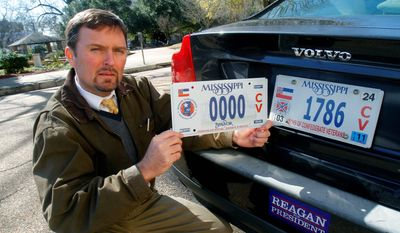 Greg Stewart, a member of the Sons of Confederate Veterans, displays a sample of the latest Civil War sesquicentennial tag that is being sold (left), adjacent to the current tag. A fight is brewing over a proposal for a license plate honoring an early leader of the Ku Klux Klan. (Associated Press)