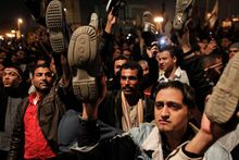 "Anti-government protesters take off their shoes and hold them in the air, symbolically saying ""Take a walk,"" in Tahrir Square in downtown Cairo on Thursday as they react to Egyptian President Hosni Mubarak's televised statement to the nation. (Associated Press)"