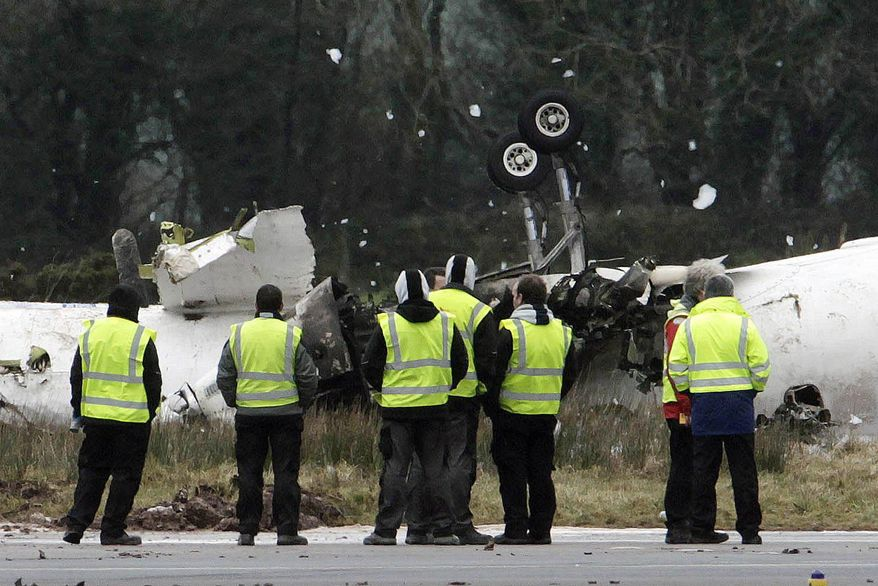 Emergency workers gather at the scene after a small commuter aircraft carrying 10 passengers and two crew crashed on Thursday, Feb. 10, 2011, as it tried to land in heavy fog at Cork Airport in Ireland. (AP Photo/Niall Carson, Press Association)