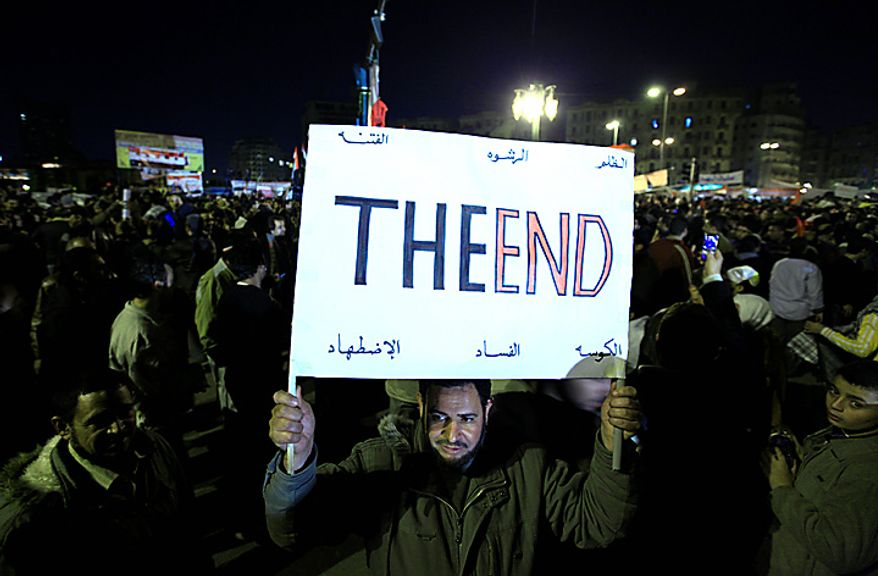 """An Egyptian anti-government protester marches with a banner reading """"the end"""" as he celebrates in Tahrir Square in downtown Cairo Thursday, Feb. 10, 2011. Egypt's military announced on national television it had stepped in to secure the country and promised protesters calling for President Hosni Mubarak's ouster that all their demands would soon be met. Tens of thousands of protesters packed in central Tahrir broke into chants of 'We're almost there, we're almost there' and waved V-for-victory signs as thousands more flowed in to join them well after nightfall. (AP Photo/Amr Nabil)"""