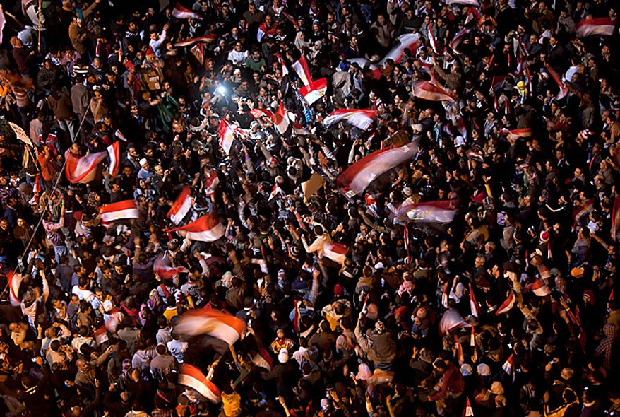 """Anti-government protesters celebrate in Tahrir Square in downtown Cairo, Egypt, Thursday, Feb. 10, 2011. Egypt's military announced on national television it had stepped in to secure the country and promised protesters calling for President Hosni Mubarak's ouster that all their demands would soon be met. Tens of thousands of protesters packed in central Tahrir broke into chants of """"We're almost there, we're almost there"""" and waved V-for-victory signs as thousands more flowed in to join them well after nightfall. (AP Photo/Emilio Morenatti)"""