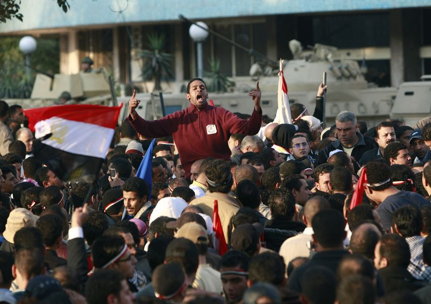 Egyptian anti-government protesters shout in front of the Egyptian television headquarters in Cairo, Egypt, on Friday, Feb. 11, 2011. (AP Photo/Ben Curtis)