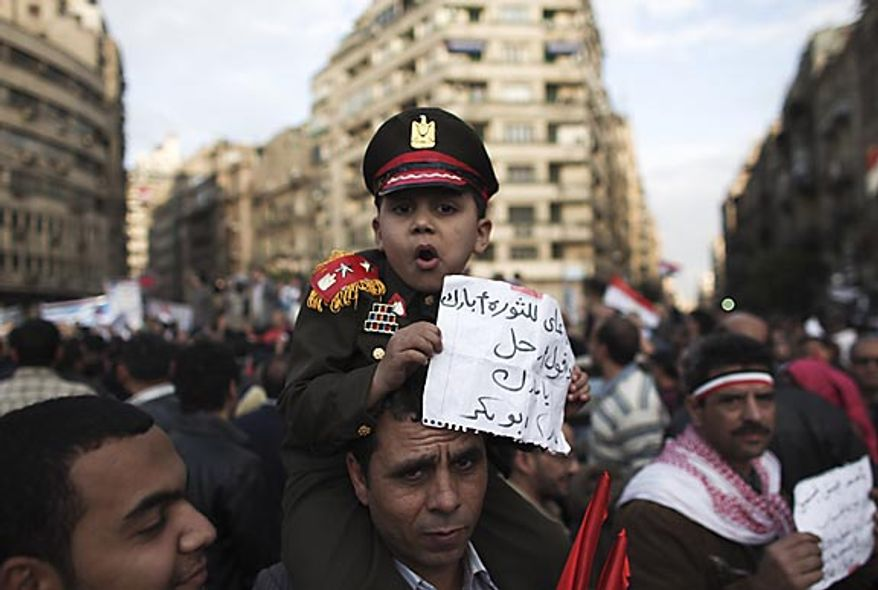 An Egyptian boy dressed as an army colonel sits on his father's shoulders in Tahrir Square in Cairo Thursday, Feb. 10, 2011.  (AP Photo/Tara Todras-Whitehill)