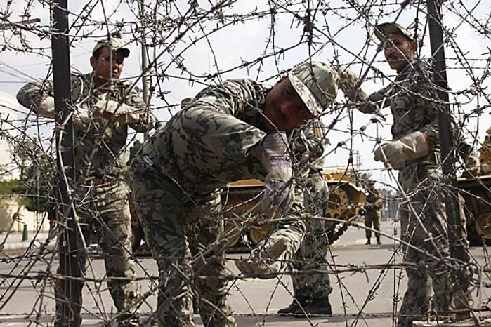 Egyptian Presidential guards block the entrence to Ettehadyya Presidential Palace with barbed wire as anti-government protesters march in Cairo Friday, Feb. 11, 2011. The Egyptian government announced later Friday that President Hosni Mubarak has stepped down. (AP Photo)