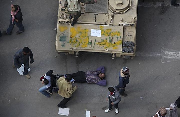 An anti-government protester lies down near an Egyptian army vehicle after traditional Muslim Friday prayers in Tahrir Square in downtown Cairo Friday, Feb. 11, 2011. The Egyptian government announced later Friday that President Hosni Mubarak has stepped down. (AP Photo/Tara Todras-Whitehill)