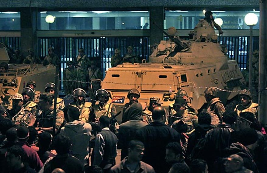 Army soldiers stand guard as anti-government protesters surround the state television building following Egyptian President Hosni Mubarak's televised speech, on the Corniche in downtown Cairo, Egypt Thursday, Feb. 10, 2011. The government announced Friday that Mr. Mubarak has stepped down. (AP Photo/Mohammed Abu Zaid)
