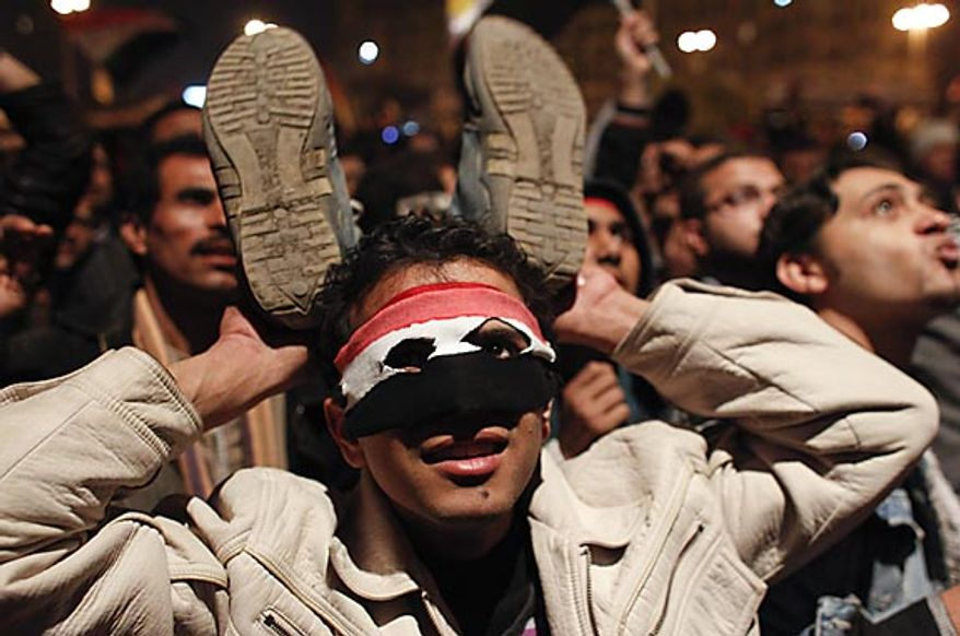 An anti-government protester in Cairo's Tahrir Square holds up his shoes in response to Egyptian President Hosni Mubarak's televised statement to the nation Thursday, Feb. 10, 2011. Mr. Mubarak stepped down Friday. (AP Photo/Tara Todras-Whitehill)
