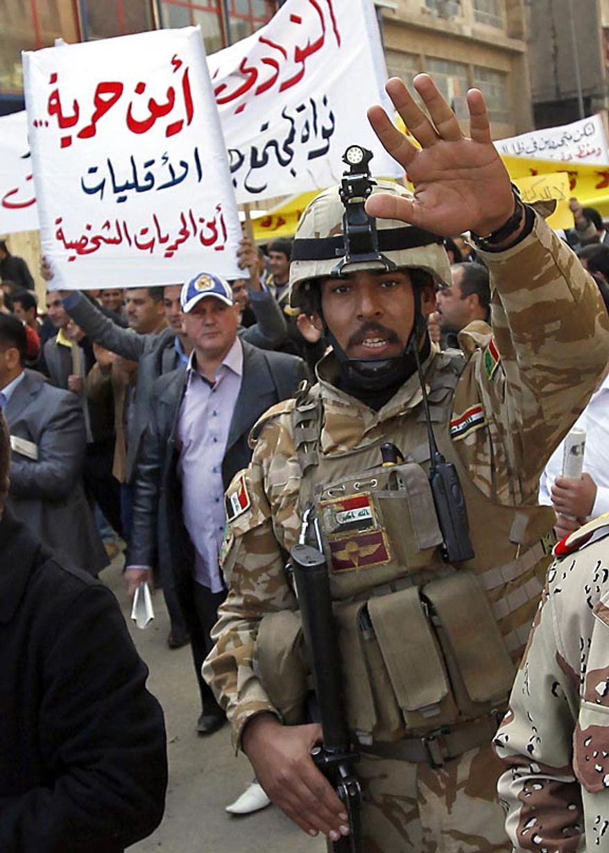"""An Iraqi army soldier attempts to prevent photographers from taking pictures while protesters chant anti-government slogans during a demonstration in Baghdad, Iraq, Friday, Feb. 11, 2011. In at least four morning demonstrations across Baghdad, protesters painted a picture of their homeland that they said has fewer services and more corruption than in Egypt. The banners in Arabic read, """"From Cairo to Baghdad, no for corruption"""" and """"Maliki, like Saddam he does not care about orphans."""" (AP Photo/Hadi Mizban)"""