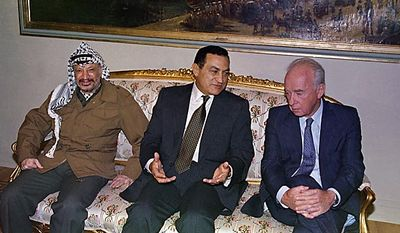 Palestine Liberation Organization Chairman Yasser Arafat, left, joins Egyptian President Hosni Mubarak and Israeli Prime Minister Yitzhak Rabin at the start of a historic meeting in Cairo on Oct. 6, 1993.  (AP Photo/Denis Paquin, File)