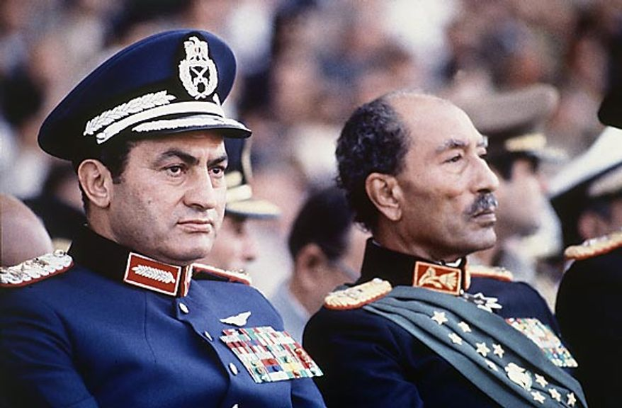 Egyptian President Anwar Sadat, right, and Vice President Hosni Mubarak are seated at the reviewing stand at a military parade just before soldiers opened fire from a truck in the parade, killing Sadat and injuring Mr. Mubarak on Oct. 6, 1981. (AP Photo/Bill Foley, File)