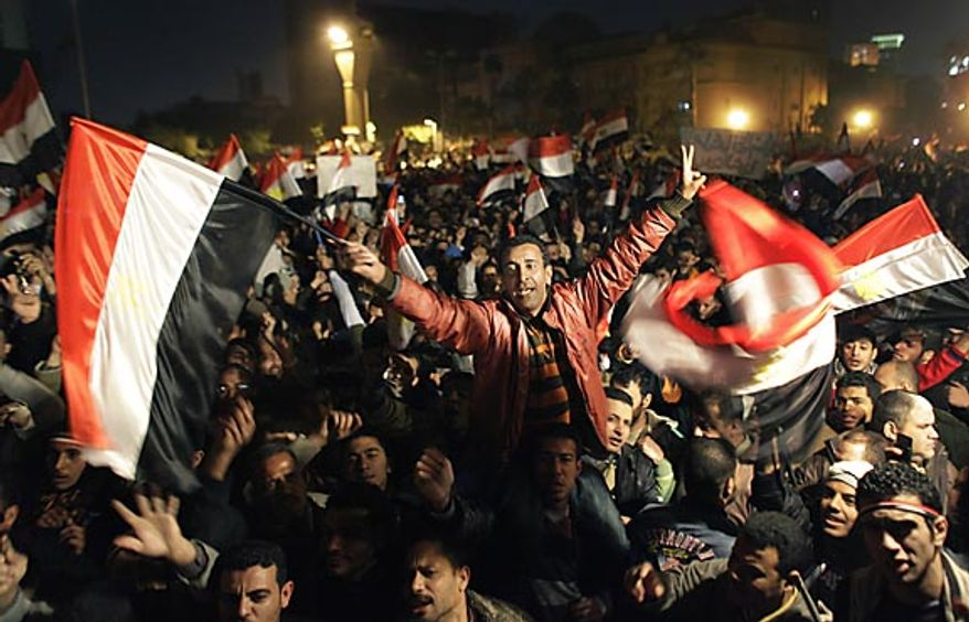**FILE** Egyptians celebrate the news of the resignation of President Hosni Mubarak, who handed control of the country to the military, at night in Tahrir Square in downtown Cairo on Feb. 11, 2011. (Associated Press)