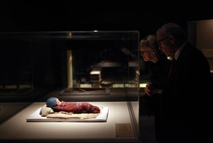 """In this March 24, 2010 file photo, Edward Roski, right, a board member at the Bowers Museum, looks at a 2,800-year-old infant mummy, Baby Bluebonnet, at the """"Secrets of the Silk Road: Mystery Mummies from China,"""" exhibit at the museum in Santa Ana, Calif. A Philadelphia museum says its exhibit on the Silk Road will go on for a limited engagement after a dispute with the Chinese government. The University of Pennsylvania Museum of Archaeology and Anthropology said Friday, Feb. 11, 2011, that the exhibit will open with a full complement of mummies and more. Some of the artifacts are more than 3,800 years old. (AP Photo/Jae C. Hong, File)"""