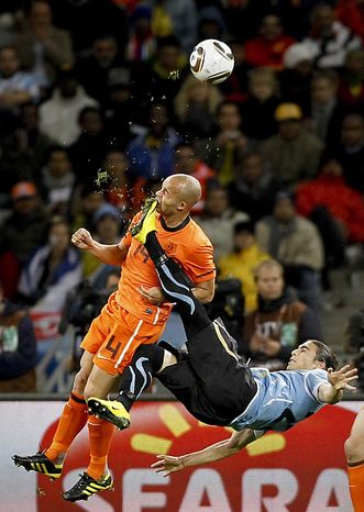 In this photo released by World Press Photo, the 1st Prize Sport Single of the 2011 World Press Photo contest by Mike Hutchings, South Africa, Reuters, shows Netherlands' Demy de Zeeuw being kicked in the face by Uruguay's Martin Ceceres during their World Cup semifinal soccer match in Cape Town, South Africa, July 6, 2010. (AP Photo/Mike Hutchings/Reuters)