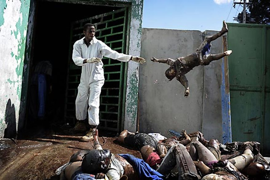 In this photo released by World Press Photo, the 1st prize General News Stories of the World Press Photo 2011 contest by Olivier Laban-Mattei, France, Agence France-Presse, shows a man throwing a dead body at the morgue of the general hospital, Port-au-Prince, Jan. 15, 2010. (AP Photo/Olivier Laban-Mattei/AFP)