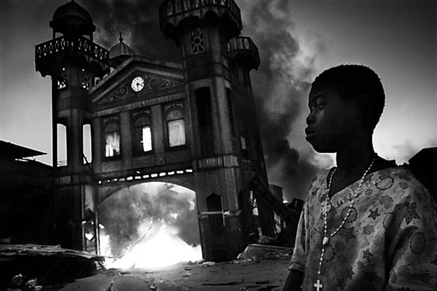 In this photo released by World Press Photo, the 1st Prize General News Single of the World Press Photo 2011 contest by Riccardo Venturi, Italy, Contrasto, shows the old Iron Market burning, Port-au-Prince, Haiti, Jan. 18, 2010.  (AP Photo/Riccardo Venturi/Contrasto)