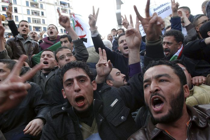 Algerian protesters chant slogans during a demonstration in Algiers, Algeria, on Saturday, Feb. 12, 2011. Thousands of people defied a government ban on demonstrations and poured into the Algerian capital for a pro-democracy rally Saturday, a day after weeks of mass protests toppled Egypt's authoritarian leader. (AP Photo/Sidali Djarboub)