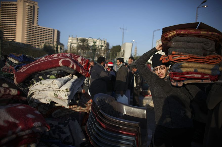 Egyptians return blankets that were donated by an Islamic charity as they break down their makeshift camps in Tahrir Square in downtown Cairo, Egypt, on Saturday, Feb. 12, 2011. (AP Photo/Tara Todras-Whitehill)