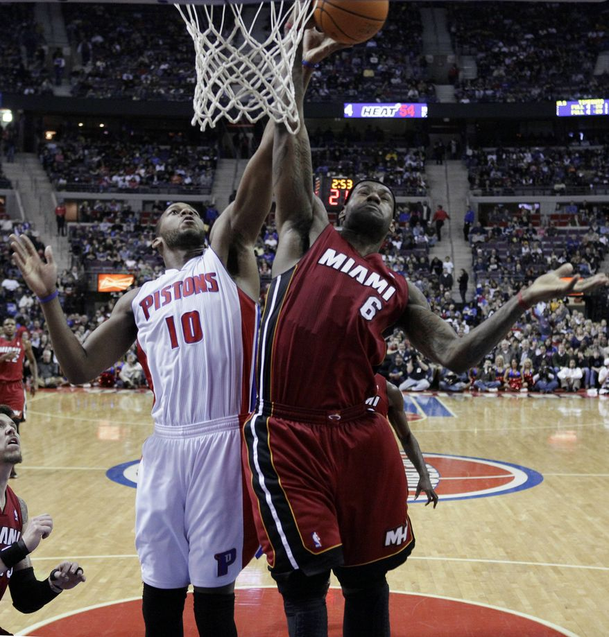 Detroit Pistons power forward Greg Monroe (10) and Miami Heat small forward LeBron James (6) battle for a rebound in the first half of their NBA basketball game in Auburn Hills, Mich., on Friday, Feb. 11, 2011. (AP Photo/Paul Sancya)