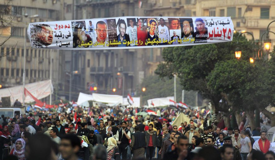 "Egyptians pass under a banner honoring people who were killed during the Jan. 25 protests, at Tahrir Square, Egypt, on Saturday, Feb. 12, 2011. The Arabic sign reads ""who is responsible for their blood."" (AP Photo/Amr Nabil)"