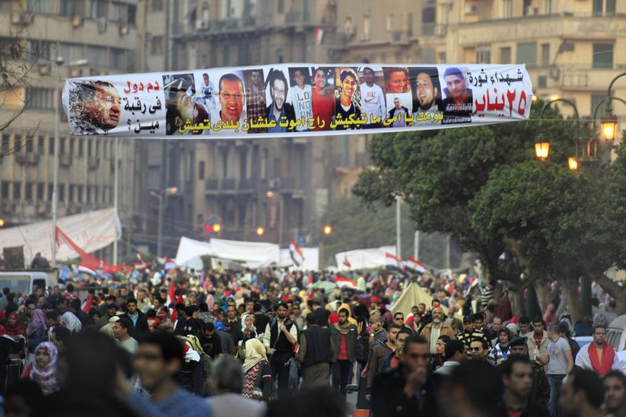 """Egyptians pass under a banner honoring people who were killed during the Jan. 25 protests, at Tahrir Square, Egypt, on Saturday, Feb. 12, 2011. The Arabic sign reads """"who is responsible for their blood."""" (AP Photo/Amr Nabil)"""