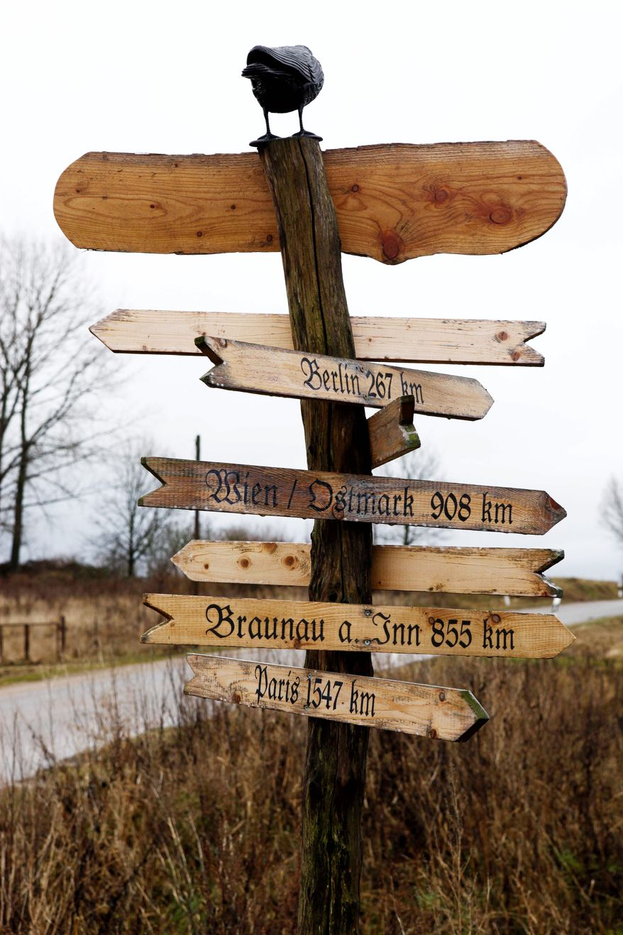 A handcrafted wooden signpost in Jamel, Germany, shows the way to Vienna, Paris and Braunau am Inn, the birthplace of Adolf Hitler in Austria.
