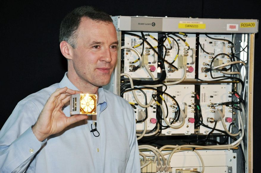 Associated Press photo Wim Sweldens, the president Alcatel-Lucent's wireless division, holds a lightRadio cube, a small cell-phone antenna that can be deployed on lampposts and buildings.