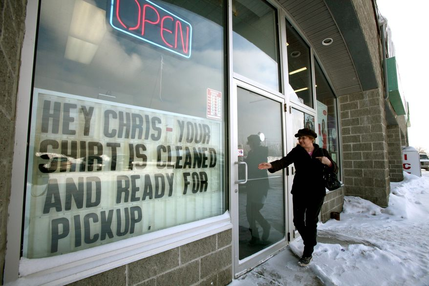 ASSOCIATED PRESS Karen Machovoe, of Lancaster, N.Y., enters a dry cleaners, where a sign pokes fun at the bare-chested-photo scandal of local Republican Rep. Christopher Lee that prompted his quick resignation.