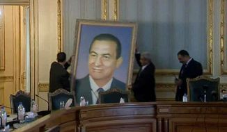 ** FILE ** Officials remove a painting of ousted Egyptian President Hosni Mubarak at the main Cabinet building in Cairo on Sunday, Feb. 13, 2011. Egyptians are removing portraits of Mr. Mubarak that have hung in public and private institutions throughout his three decades in power. (Associated Press)