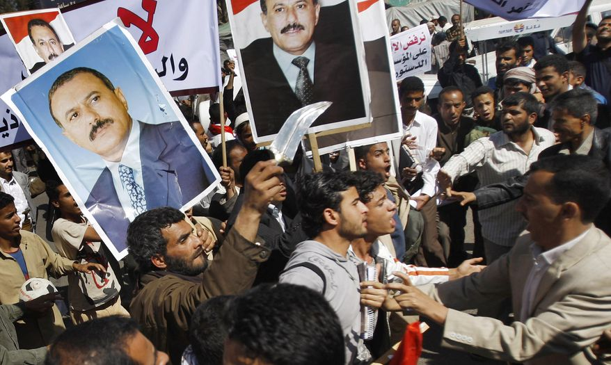 Yemeni anti-government protestors (right) scuffle with government supporters during a rally demanding political reform and the resignation of President Ali Abdullah Saleh in Sanaa, Yemen, on Sunday, Feb. 13, 2011. (AP Photo/Hani Mohammed)