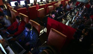 **FILE** People use computers at an Internet cafe in Fuyang, in central China's Anhui province, on March 12, 2010. Experts say security for many computers in China is so poor that they are vulnerable to being taken over and used to hide the source of attacks from elsewhere. (Associated Press)