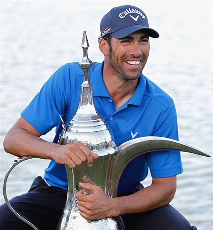 Spain's Alvaro Quiros holds the trophy after he won the final round of the Dubai Desert Classic Golf Tournament at the Emirates Golf Club in Dubai, United Arab Emirates, Sunday, Feb. 13, 2011. (AP Photo/Nousha Salimi)