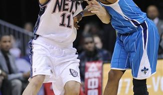 New Jersey Nets' Brook Lopez, left, passes the ball by New Orleans Hornets' Chris Paul during the fourth quarter of an NBA basketball game Wednesday, Feb. 9, 2011 in Newark, N.J. The Nets won 103-101 in overtime. (AP Photo/Bill Kostroun)