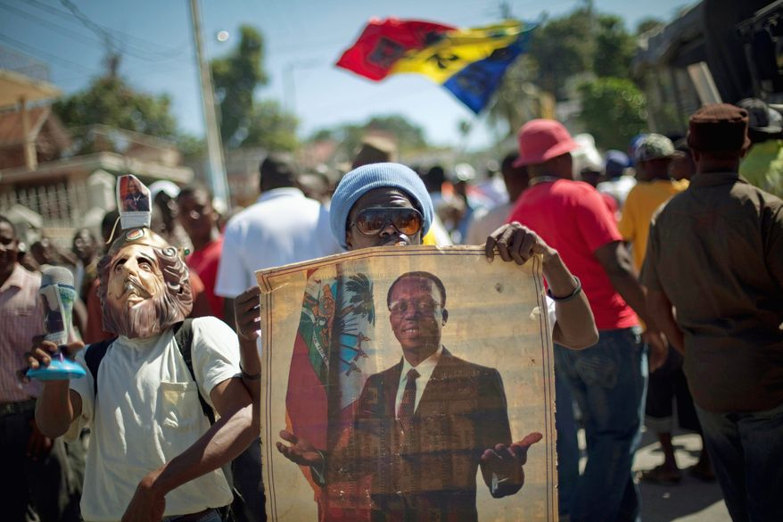 A Haitian holds up a picture of ousted ex-President Jean-Bertrand Aristide at a Feb. 2 protest in Port-au-Prince demanding his return. (Associated Press)