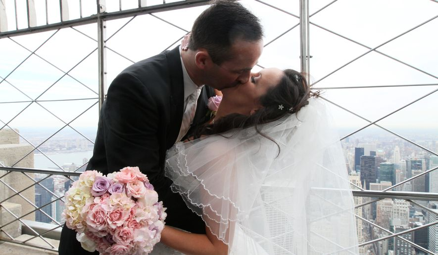 Newlyweds George Callahan and Sarah-Marie Carpino, from Lindenhurst, N.Y., seal the deal at the Empire State Building in New York. They were one of 14 couples wed Monday at the 17th annual Empire State Building/TheKnot.com Valentine's Day wedding event. (Associated Press)